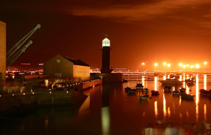 İspanya'da gezilecek yerler- Limanda eğlenen insanların gölgeleriyle kızıl bir yaz akşamında Vigo.