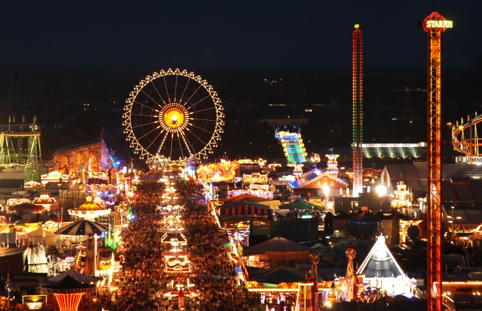 Oktoberfest gecenin içinde parlarken binlerce insan Oktoberfest'in atraksiyonlarını ziyaret ediyor.